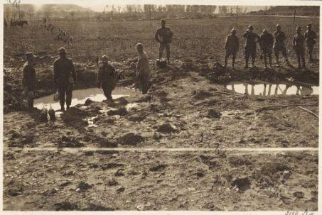Attingendo acqua in una buca scavata da una granata
