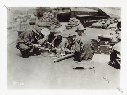 Soldati che puliscono gli ingranaggi di un arma